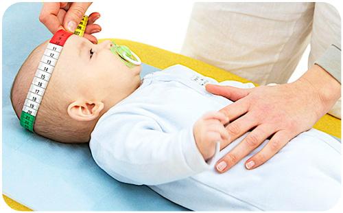 малышу измеряют головку