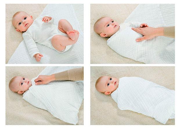 мама пеленает новорожденного