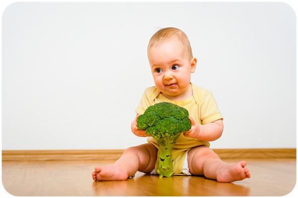 ребенок кушает брокколи