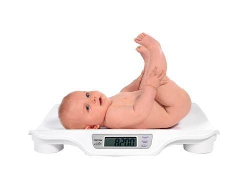 младенца взвешивают на весах